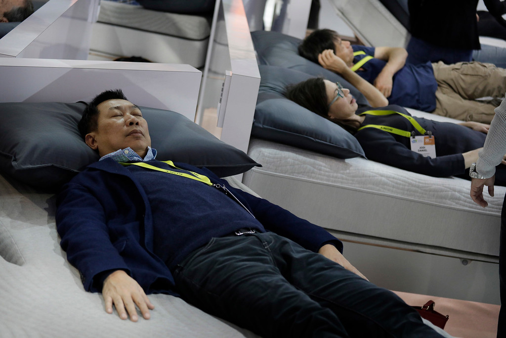 . Attendees lie on the Sleep Number 360 Smart Bed during CES International, Saturday, Jan. 7, 2017, in Las Vegas. The bed has sensors that adjust the comfort and firmness depending on the user\'s position. It also warms the foot area prior to bedtime and it can sense snoring and automatically adjust the bed to stop it. (AP Photo/John Locher)
