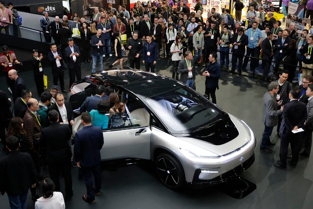 . People gather around the Faraday Future\'s FF91 electric car at CES International Thursday, Jan. 5, 2017, in Las Vegas. (AP Photo/Jae C. Hong)