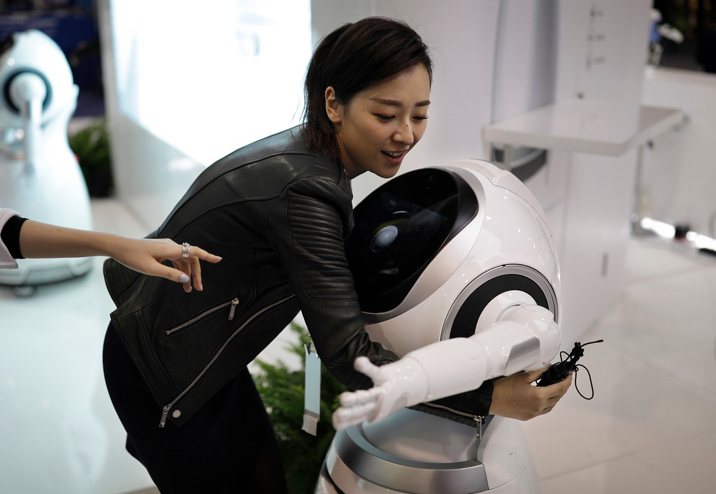 . Ting Wu gets a hug from the Cruzr cloud-based service robot at the Ubtech booth during CES International, Saturday, Jan. 7, 2017, in Las Vegas. (AP Photo/John Locher)