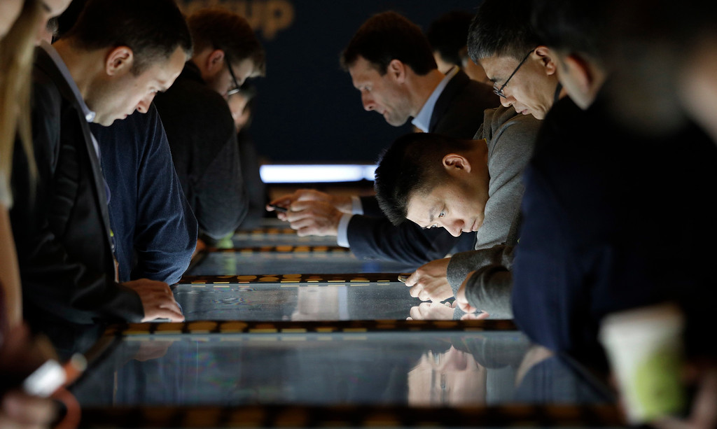 . People look at gadgets during CES International, Saturday, Jan. 7, 2017, in Las Vegas. (AP Photo/John Locher)