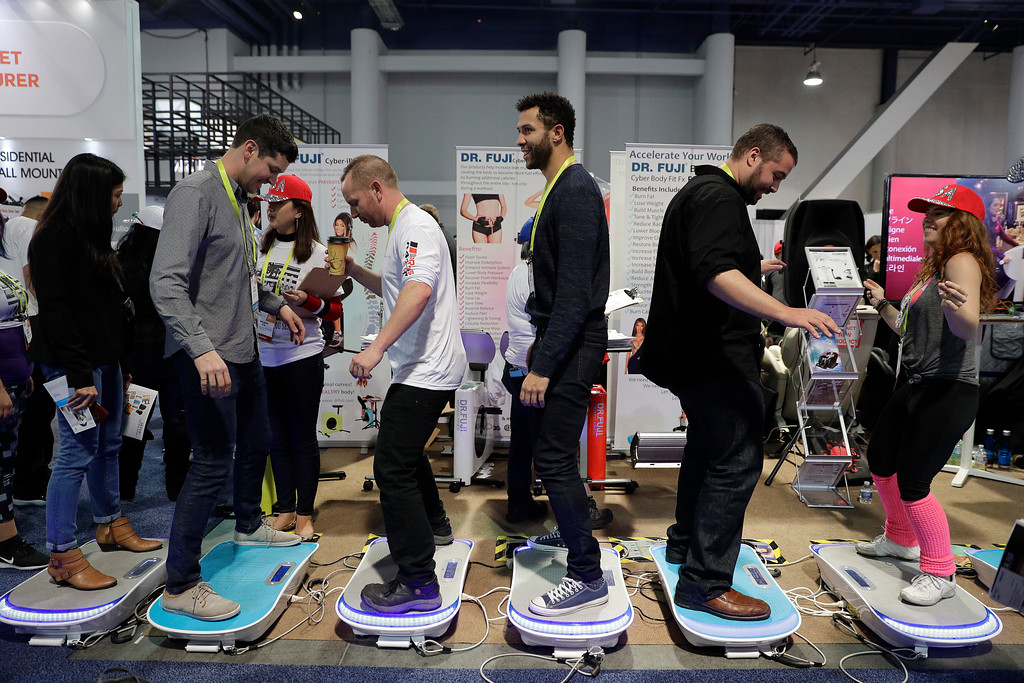 . Show attendees try out vibration fitness machines at CES International, Thursday, Jan. 5, 2017, in Las Vegas. (AP Photo/Jae C. Hong)