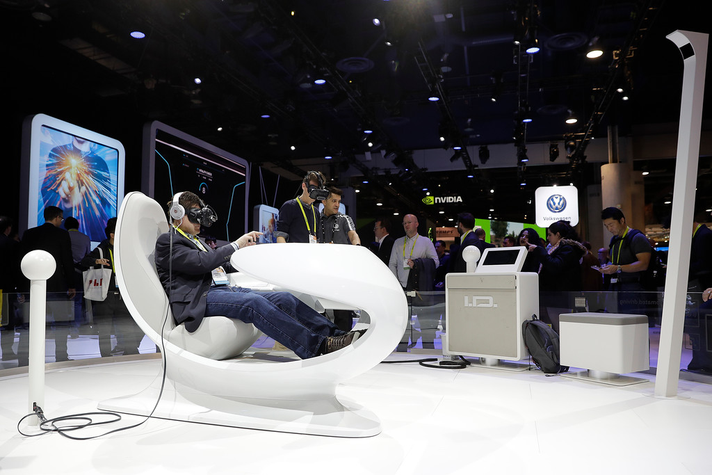 . Show attendees watch a presentation using VR headsets at the Volkswagen booth at CES International Thursday, Jan. 5, 2017, in Las Vegas. (AP Photo/Jae C. Hong)