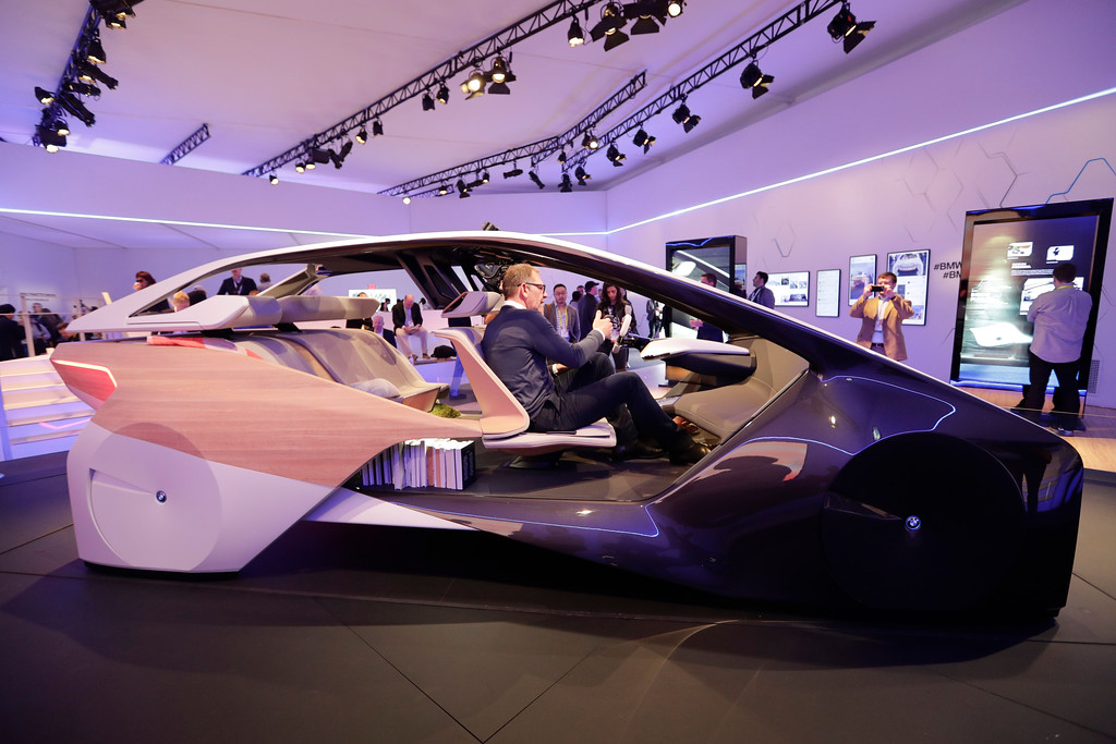 . Holger Hampf, BMW\'s head of user experience, front, and a reporter sit in the BMW i Inside Future concept, at CES International Thursday, Jan. 5, 2017, in Las Vegas. (AP Photo/Jae C. Hong)