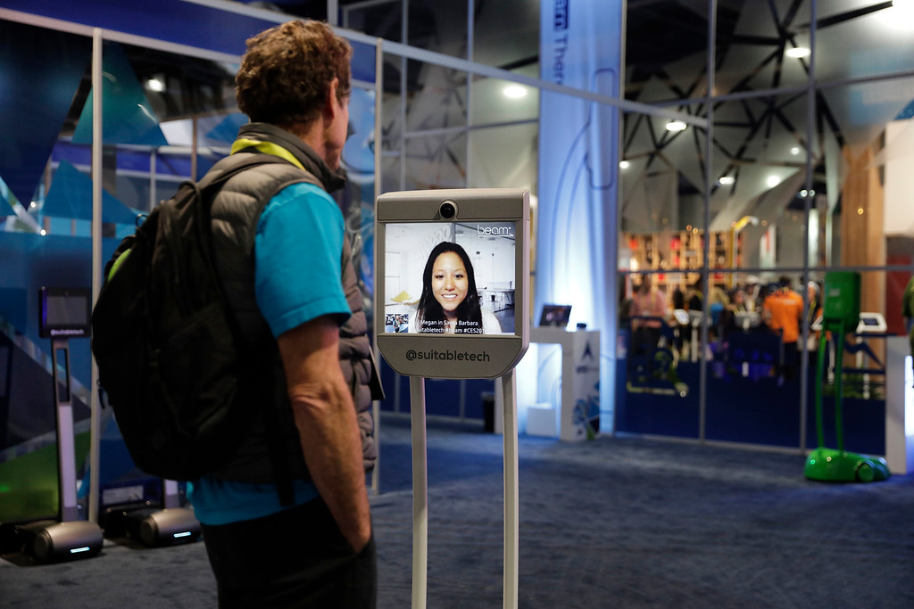 . An attendee speaks with a women remotely via a Beam mobile independent telecom device at the Suitable Technologies booth during CES International, Thursday, Jan. 5, 2017, in Las Vegas. (AP Photo/John Locher)