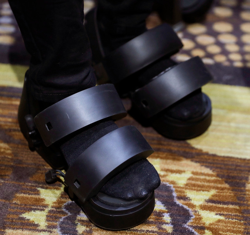 . A woman wears Taclim VR shoes at the Cerevo booth during CES Unveiled before CES International, Tuesday, Jan. 3, 2017, in Las Vegas. The shoes have haptic feedback. (AP Photo/John Locher)