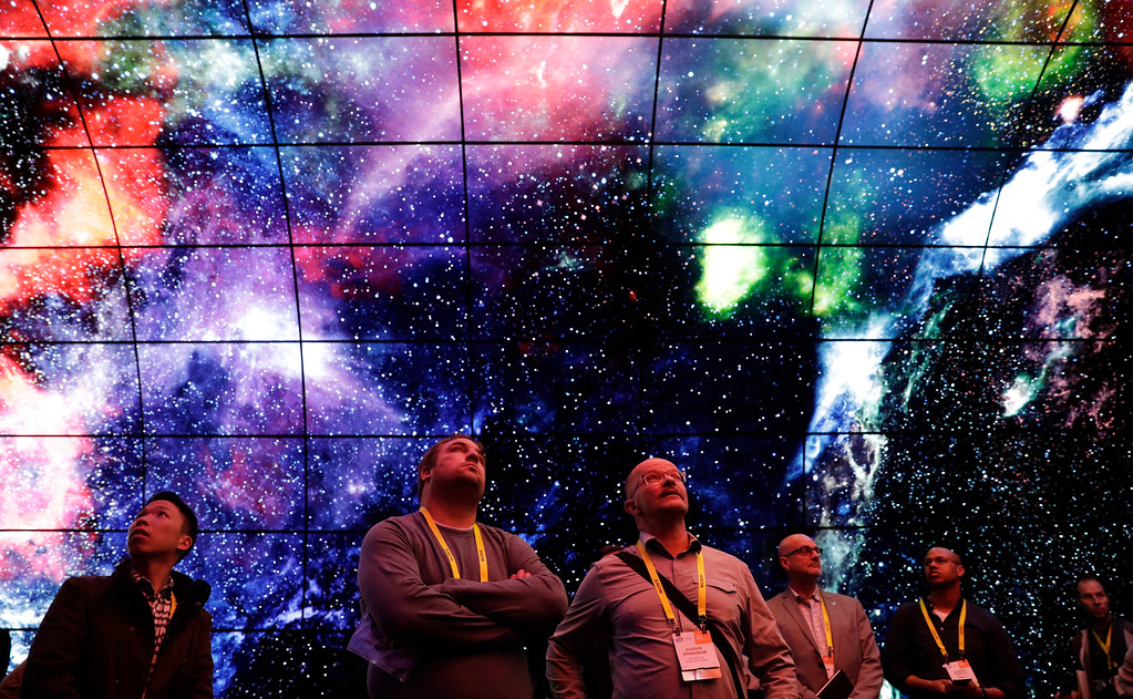 . Attendees take pictures in an exhibit of LG OLED 4K TVs at the LG booth during CES International, Thursday, Jan. 5, 2017, in Las Vegas. (AP Photo/John Locher)