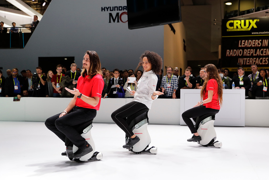 . Models sit the Honda UNI-CUB electric scooters at CES International Thursday, Jan. 5, 2017, in Las Vegas. (AP Photo/Jae C. Hong)