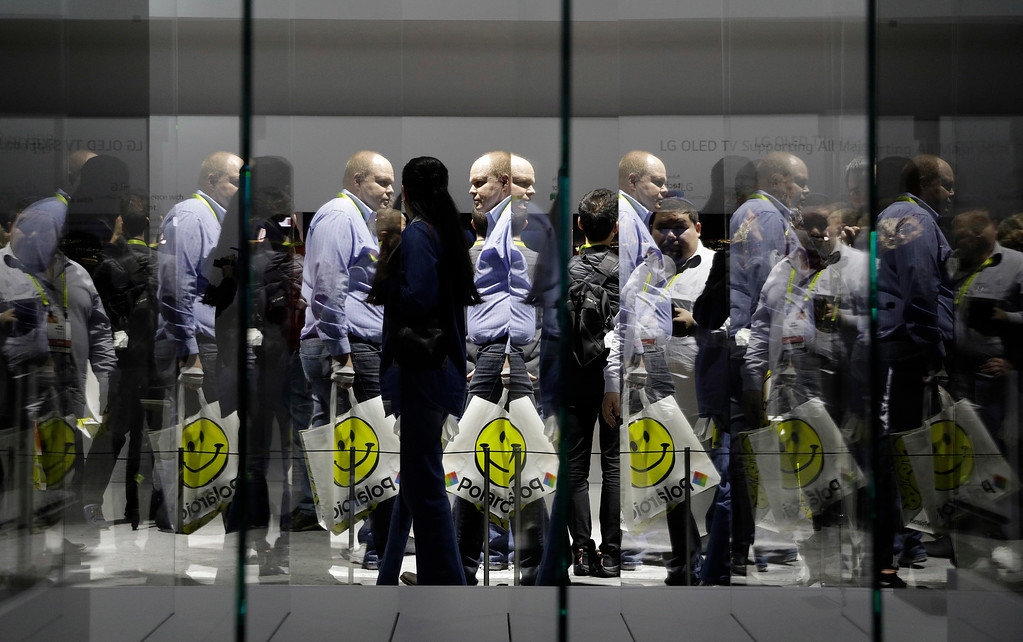 . People are reflected in the glass of a display for the LG Signature OLED TV W at the LG booth during CES International, Thursday, Jan. 5, 2017, in Las Vegas. (AP Photo/John Locher)