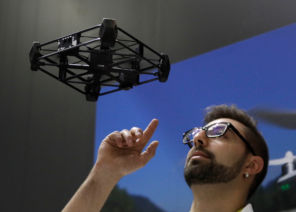 . Alex Shapilsky flies the AEE Rova drone near his head at the AEE booth during CES International, Thursday, Jan. 5, 2017, in Las Vegas. (AP Photo/John Locher)