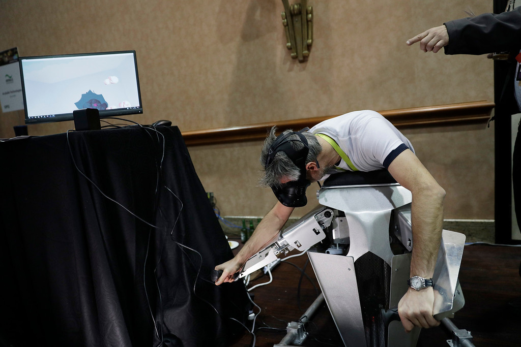 . Laurent Thiry demonstrates the Hypersuit virtual realty controller during CES Unveiled before CES International, Tuesday, Jan. 3, 2017, in Las Vegas. The controller simulates flying in the VR environment. (AP Photo/John Locher)