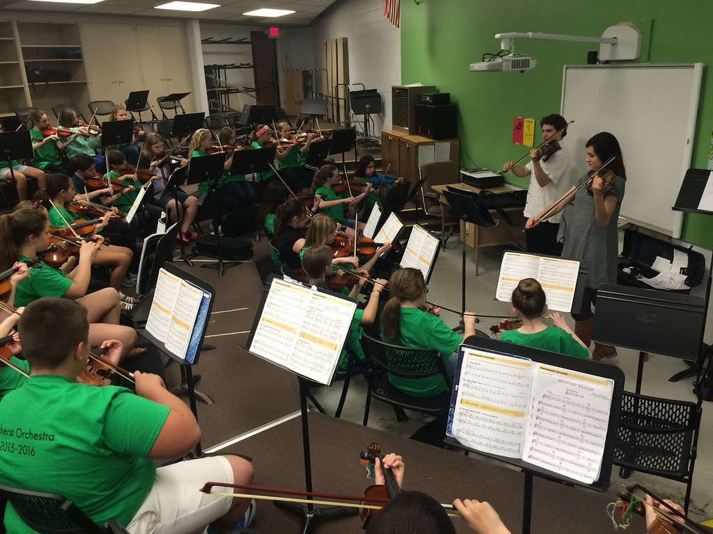 . Submitted photo - Northern Ohio Youth Orchestra <br> Northern Ohio Youth Orchestra coaches Greg Gennaro and Kimberly Bill coach the Amherst orchestra violin section on April 25, 2016. The Northern Ohio Youth Orchestra and Amherst schools collaborated for an evening of studying strings at Nord Middle School. Students in grades five and six received coaching from NOYO staff.