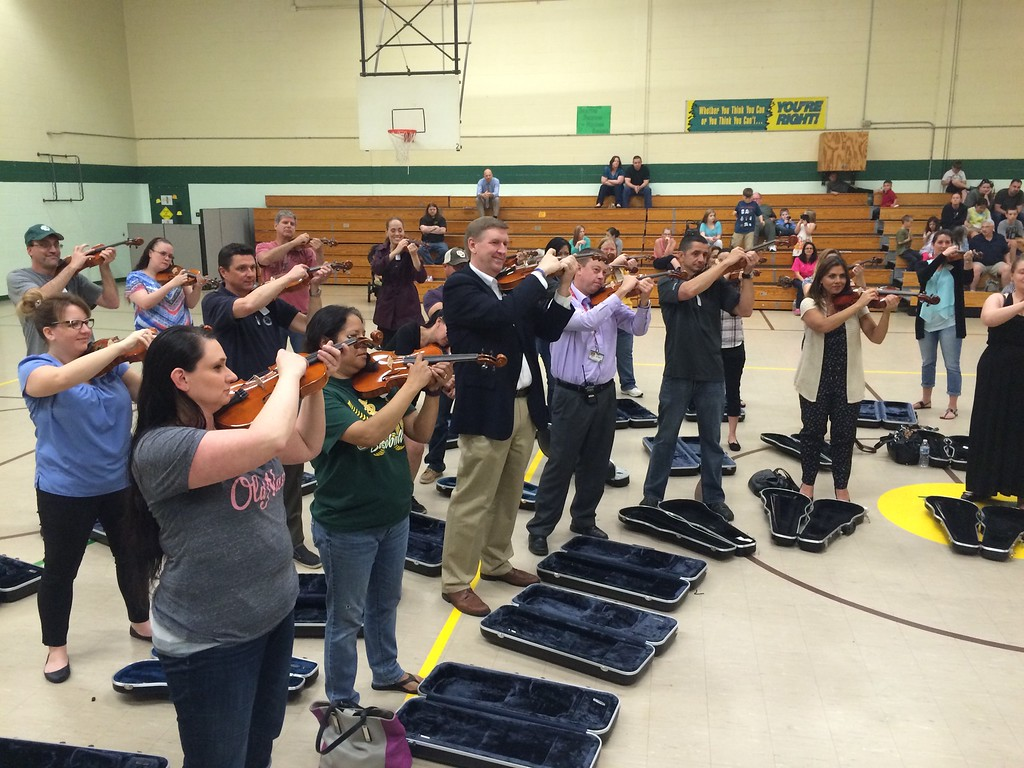 . Submitted photo - Northern Ohio Youth Orchestra <br> Amherst Schools Superintendent Steve Sayers and Principal Bill Miller stand with parents learning to play violin on April 25, 2016. The Northern Ohio Youth Orchestra and Amherst schools collaborated for an evening of studying strings at Nord Middle School. Students in grades five and six received coaching from NOYO staff.