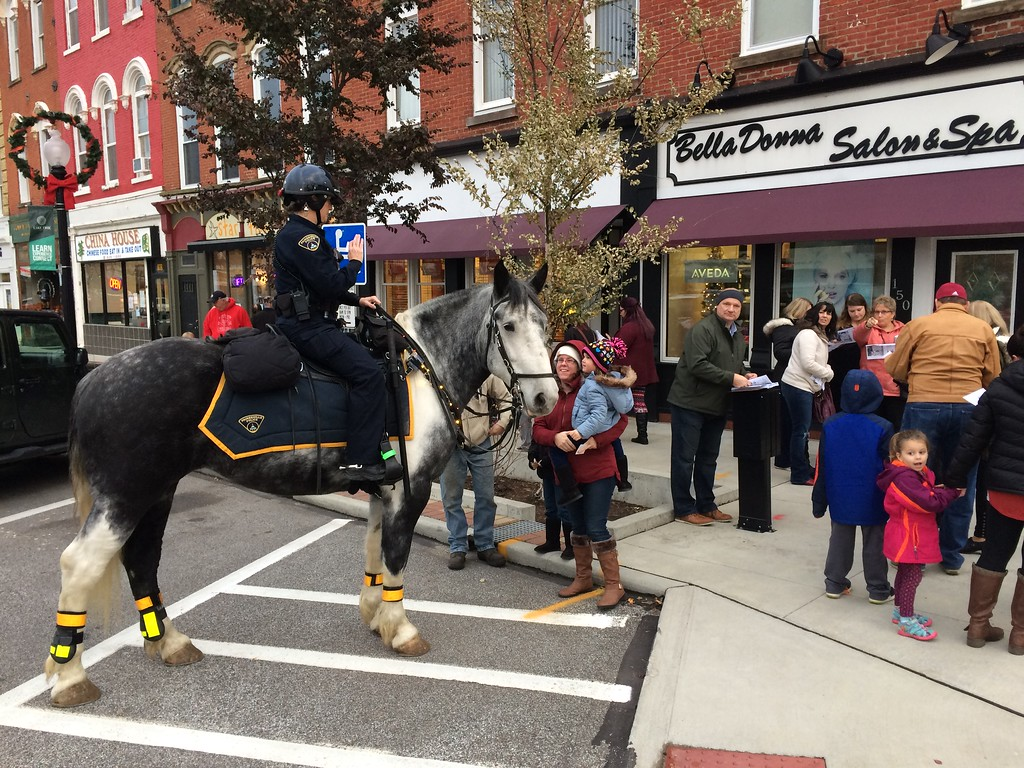 . Painesville police officer Taya Workum sits atop Opal, a Spotted Draft horse, as residents get a closer look during the Downtown Painesville Organization\'s Holiday Open House on Nov. 14. The event attracted hundreds of people and officially kicked off the city\'s holiday season with its annual tree lighting ceremony. (Chad Felton � The News-Herald)