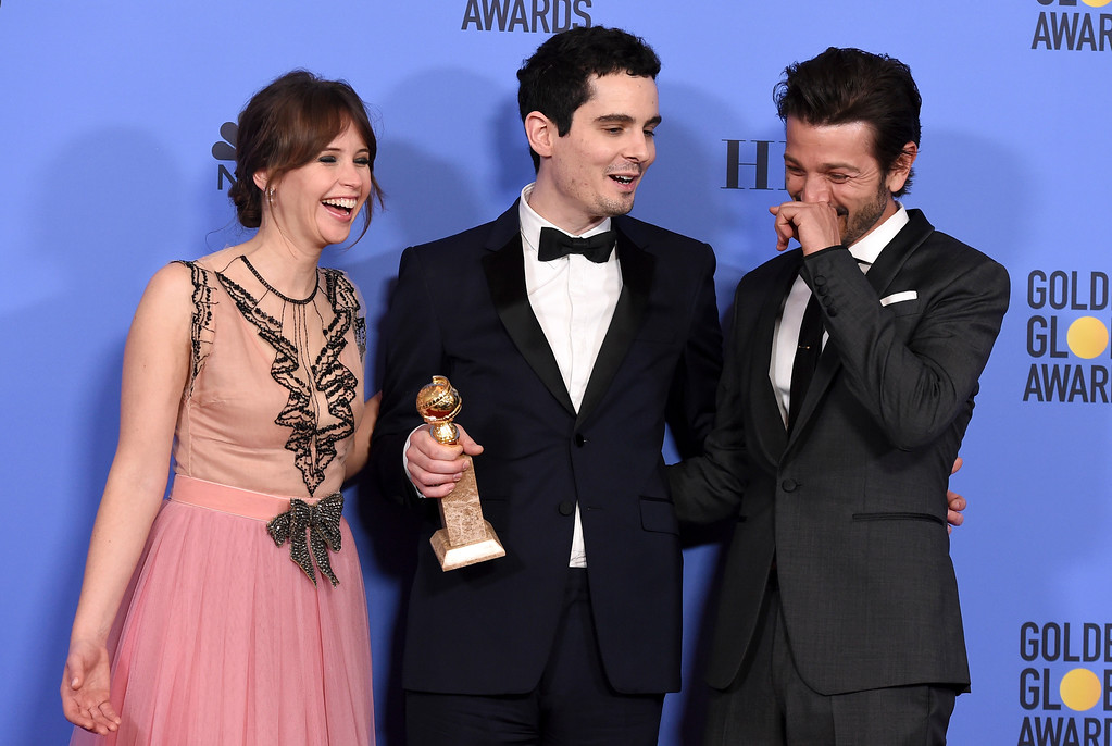 """. Damien Chazelle, center, winner of the award for best screenplay - motion picture for \""""La La Land\"""" poses with presenters Felicity Jones, left, and Diego Luna at the 74th annual Golden Globe Awards at the Beverly Hilton Hotel on Sunday, Jan. 8, 2017, in Beverly Hills, Calif. (Photo by Jordan Strauss/Invision/AP)"""