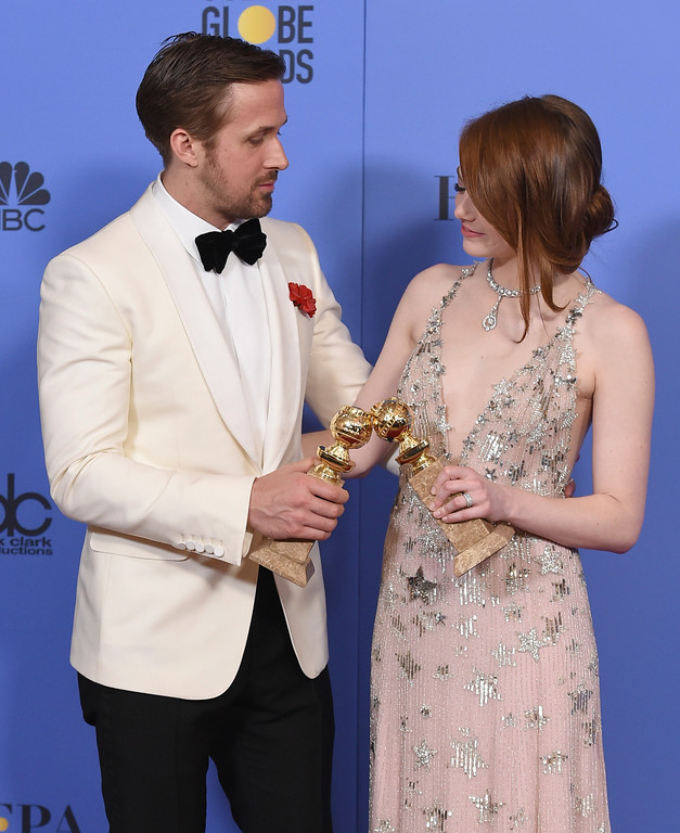 """. Ryan Gosling, left, and Emma Stone pose in the press room with the award for best performance by an actor and actress in a motion picture - musical or comedy for \""""La La Land\"""" at the 74th annual Golden Globe Awards at the Beverly Hilton Hotel on Sunday, Jan. 8, 2017, in Beverly Hills, Calif. (Photo by Jordan Strauss/Invision/AP)"""