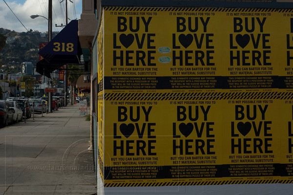 RB_BuyLoveHere__052710_1074w.jpg<br /> <br /> Buy Love Here posters glued to a wall on La Cienega Boulevard to promote British comic and actor Russell Brand's pop-up store event filmed for his upcoming documentary on consumerism and happiness