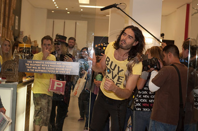 """Russell Brand_BuyLoveHere__052710_1032w .jpg  British Comic, Actor, Author and subject of an upcoming documentary on consumerism and happiness, Russell Brand, hosts a pop-up store filmed as part of his documetary. Brand acted as a vendor and interviewed people who came to the pop-up store to swap their unwanted goods for donated stock. Also pictured in the store are gossip blogger Perez Hilton and Shepard Fairey of Obama """"Hope"""" campaign poster fame. Russell Brand beckons more people in the waiting crowd to enter the pop-up store to swap items."""