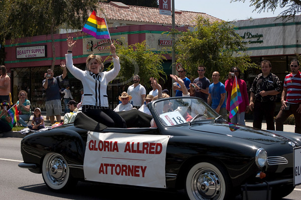 "GloriaAllred_LAPride_061310_1025<br /> <br /> Well-known attorney Gloria Allred rides in a black convertible and holds a rainbow flag, a symbol of the gay community at The Los Angeles Pride Parade takes place on Santa Monica Boulevard in West Hollywood, CA June 13, 2010. Gloria Allred is driven by a male driver in drag in a matching outfit and wig to serve as a Gloria Allred look-allike. The front of the car they drove had a sign which read ""The Glorias."""