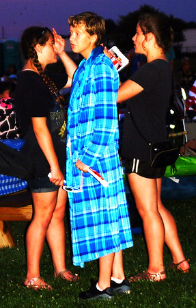 Debbie Blank | The Herald-Tribune<br /> How do you stay dry during a sprinkle? Toss on a robe you found in your car trunk. That's what Abigail Spurgeon did. With her are twins Leah (left) and Kaitlynn Cole, 13.