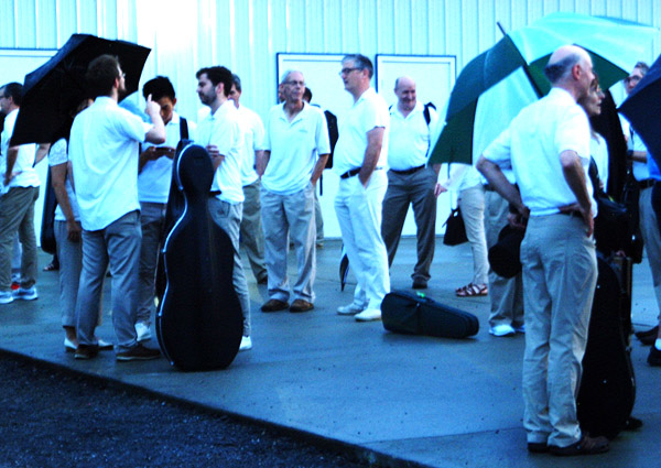 Debbie Blank   The Herald-Tribune<br /> After the rain let up, musicians stood in a parking lot while stagehands dried off the stage.