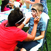 Debbie Blank | The Herald-Tribune<br /> Church on Fire volunteer Tarra Ortman, Napoleon, begins to draw a golden retriever on the face of Noah Blankinship, 7, Batesville.