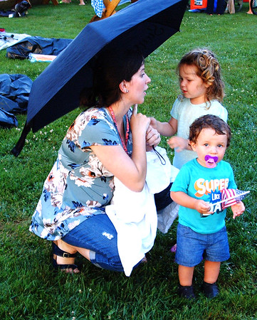 Debbie Blank | The Herald-Tribune<br /> Mom Mary Hartman, Batesville, keeps rain off Sage, 2, and Martin, 1.