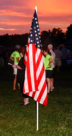 Debbie Blank | The Herald-Tribune<br /> Volunteers in lime green shirts gather near a flag at sunset.