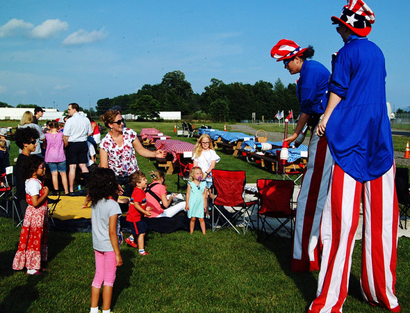 "Debbie Blank | The Herald-Tribune<br /> As area residents arrived at Bill Gillespie Soccer Park Saturday, July 6, to watch ""Star-Spangled Symphony,"" patriotic clowns on stilts amused the kids around 6:30 p.m."