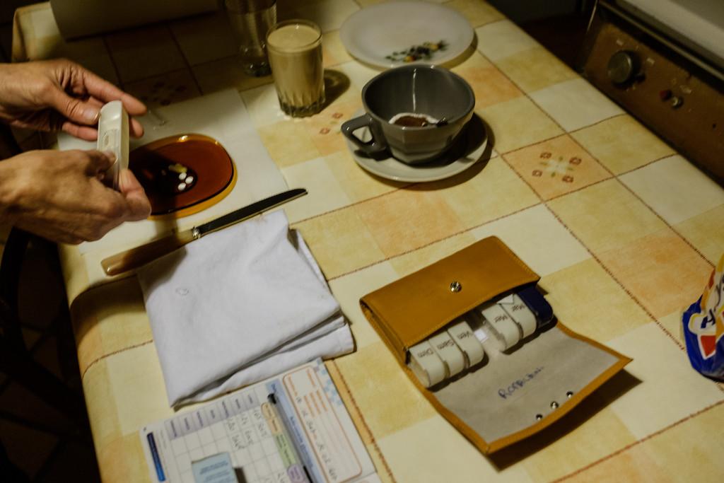 Béatrice prépare les médicaments pour Mme Romaldini. Chaque pilulier est marqué et un carnet est tenu avec précision.
