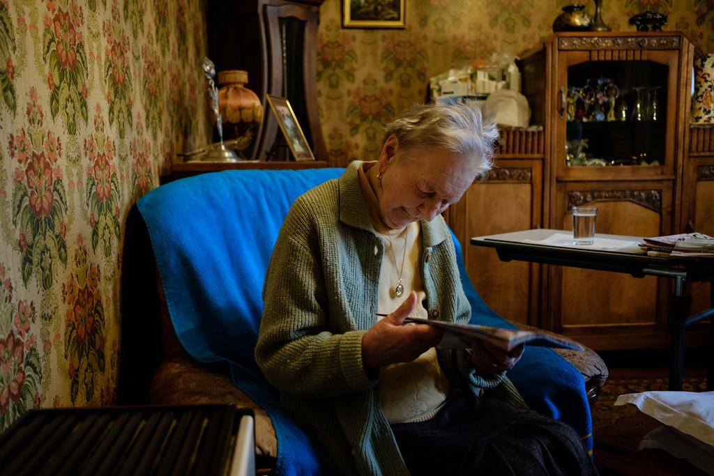 """C'est le temps de la lecture ! Après un bon déjeuner, une toilette et des soins pour ses jambes, Mme Romaldini peut prendre plaisir dans son salon à lire son journal. Sans lunettes, et en commentant les titres. <br /> La récompense d'un travail bien fait ! Béatrice reviendra vers midi lui préparer son repas et lui apporter des courses. Elle lui rapportera mouchoirs et serviettes bien repassées, un petit extra à l'oeil. """"Nous essayons de ne pas changer ses habitudes et qu'est-ce que ça nous coûte?"""""""