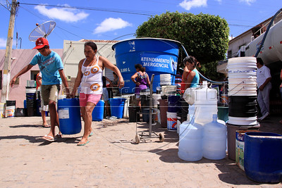 Residents of Sao Jose do Egito, Pernambuco state,  fill water buckets from neighborhood tanks. With the local reservoirs dry, all water in the city in the Semi-arid region known as the sertao must be trucked in. Those who can afford it pay to have their home cisterns filled, while others must get wait for government trucks to fill the community tanks. The region has dry season every year, but 2012 is considered the worst in 30 years. (Australfoto/Douglas Engle)