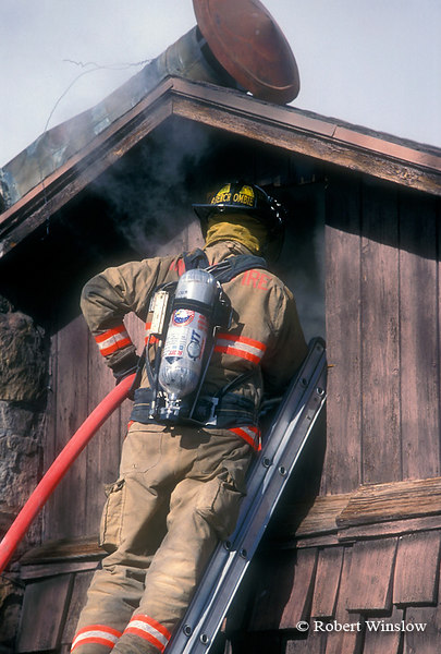Firefighter using Water Hose to Put out House on Fire, Colorado