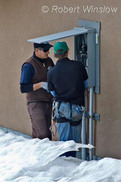 Model Released, Workers examine existing electrical panel prior to installation of photovoltaic panels and inverter, Durango, Colorado, USA, North America