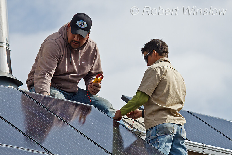 Model Released,Technicians, one Mexican American,  testing electrical connections for Schuco 180 W, model MPE 18- MS 05 Photovoltaic Panels on a South Facing Roof, Durango, Colorado, USA, North America