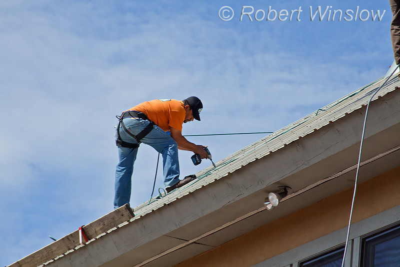 Model Released, Worker preparing to install Photovoltaic Panels on a South Facing Roof, Durango, Colorado, USA, North America