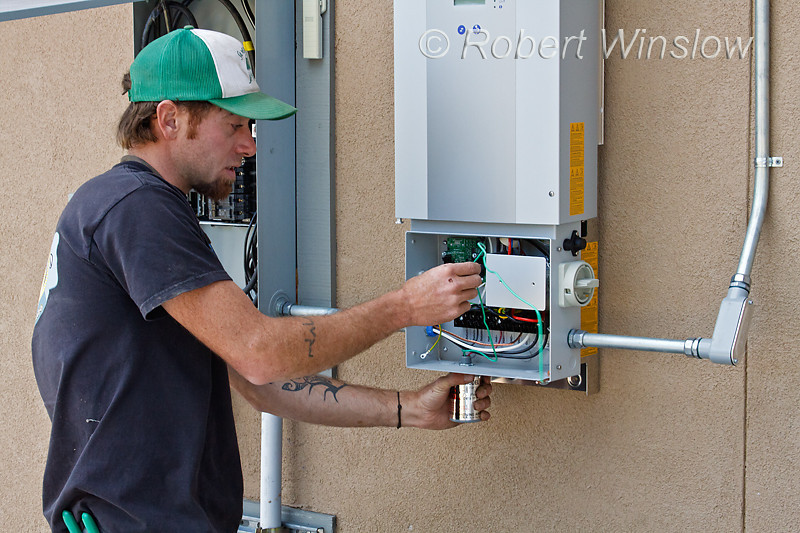 Model Released, Technician preparing electrical connections in the Kaco blueplanet 5002xi Grid-tied inverter installed for photovoltaic solar panels, Durango, Colorado, USA, North America