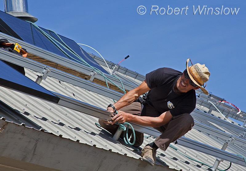 Model Released, Worker Checking alignment of panels while installing Schuco 180 W, model MPE 18- MS 05 Photovoltaic Panels on a South Facing Roof, Durango, Colorado, USA, North America