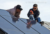 Model Released,Technicians testing electrical connections for Schuco 180 W, model MPE 18- MS 05 Photovoltaic Panels on a South Facing Roof, Durango, Colorado, USA, North America