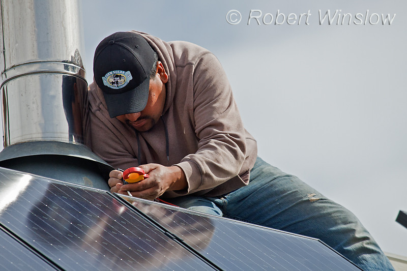 Model Released, Mexican-American Worker checking electrical circuit, installing Schuco 180 W, model MPE 18- MS 05 Photovoltaic Panels on a South Facing Roof, Durango, Colorado, USA, North America