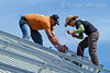 Model Released, Workers installing electircal wire preparing to install Photovoltaic Panels on a South Facing Roof, Durango, Colorado, USA, North America