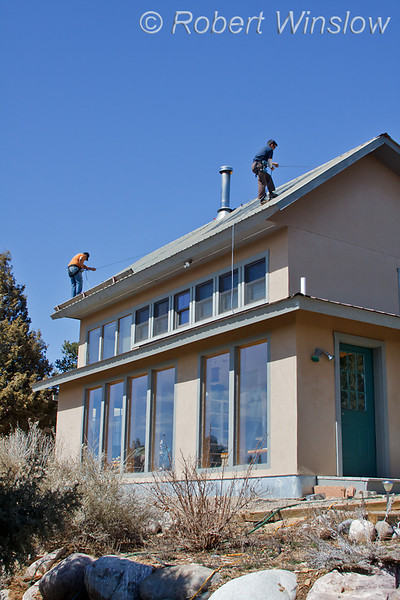 Model Released, Workers preparing to install Photovoltaic Panels on a South Facing Roof, House is also passive solar, Durango, Colorado, USA, North America