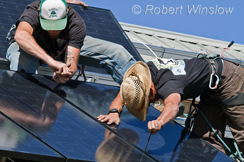 Model Released, Workers installing Schuco 180 W, model MPE 18- MS 05 Photovoltaic Panels on a South Facing Roof, Durango, Colorado, USA, North America