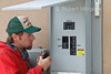 Electrician checking Main Circuit Breakers to Residential House while installing Photovoltaic Panels