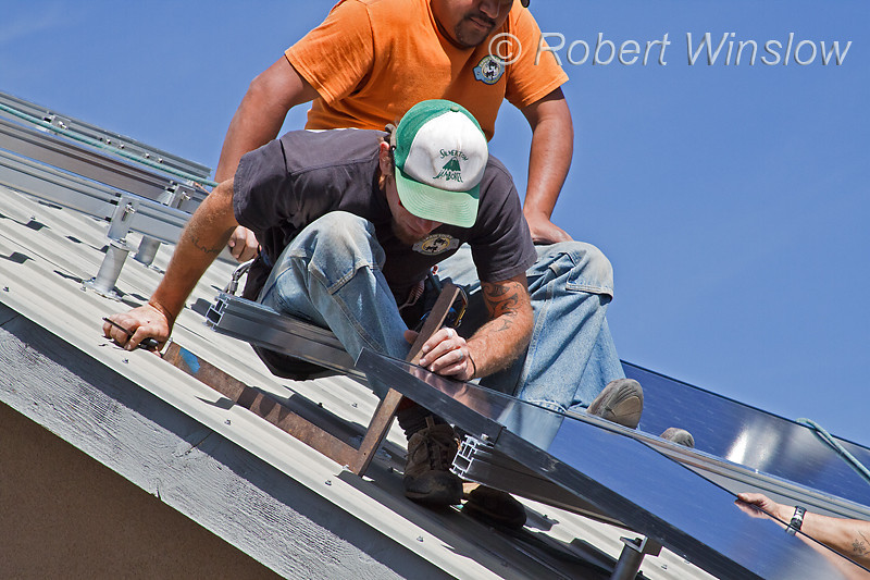 Model Released, Workers Checking Square angle installing Schuco 180 W, model MPE 18- MS 05 Photovoltaic Panels on a South Facing Roof, Durango, Colorado, USA, North America