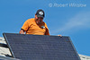 Model Released, Mexican-American Worker installing Schuco 180 W, model MPE 18- MS 05 Photovoltaic Panels on a South Facing Roof, Durango, Colorado, USA, North America