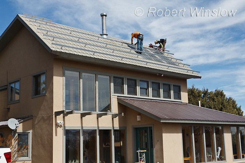 Model Released, Workers installing framework to hold Photovoltaic Panels on a South Facing Roof, Durango, Colorado, USA, North America