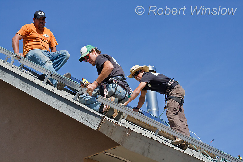 Model Released, Workers installing roof racking for  Photovoltaic Panels on a South Facing Roof, Durango, Colorado, USA, North America