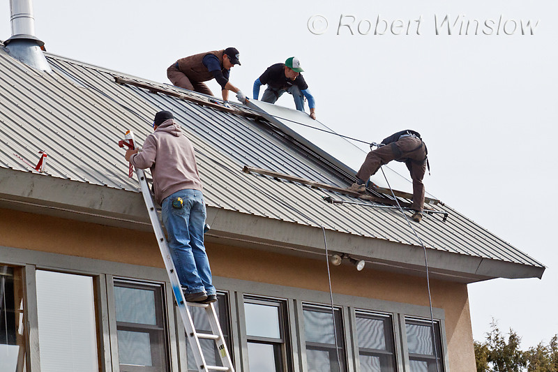 Model Released, Property Release, Workers Removing Old Hot Water Solar Panels to install photovoltaic panels, Durango, Colorado, USA, North America