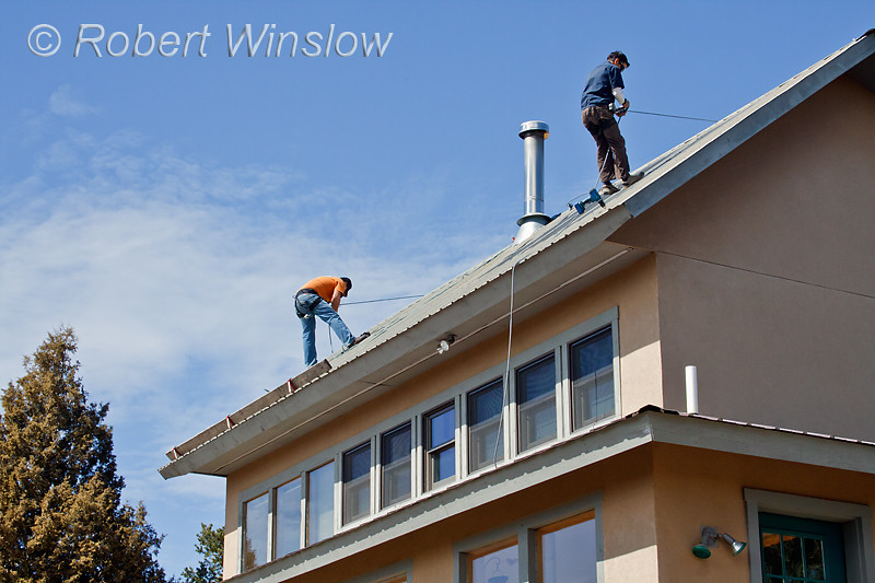 Model Released, Workers preparing to install Photovoltaic Panels on a South Facing Roof, Durango, Colorado, USA, North America