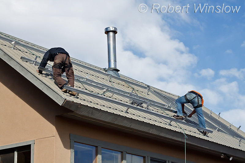 Model Released, Workers installing Racking Framework to hold Photovoltaic Panels on a South Facing Roof, Durango, Colorado, USA, North America